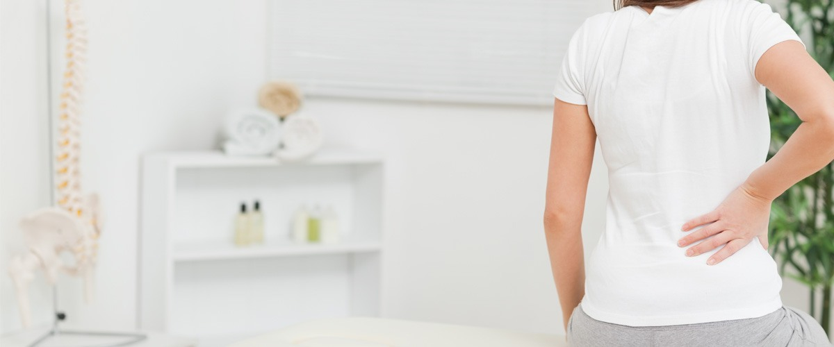 Woman siting on a table while touching her back